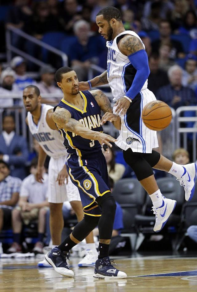 Indiana Pacers' George Hill, center, passes the ball as he is caught between Orlando Magic's Arron Afflalo, left, and Jameer Nelson, right, during the first half of an NBA basketball game in Orlando, Fla., Sunday, Feb. 9, 2014. (AP Photo/John Raoux)