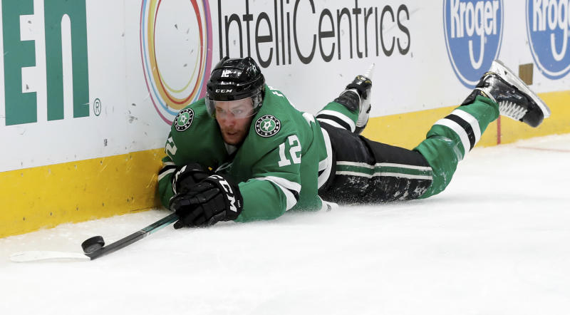 Dallas Stars center Radek Faksa (12) reaches out to control the puck after being tripped in the first period of an NHL hockey game against the Washington Capitals in Dallas, Saturday, Oct. 12, 2019. (AP Photo/Tony Gutierrez)