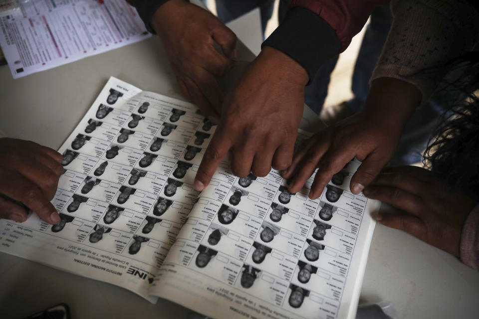 Indigenous Tzotzil people checks their names on a list during a non-binding national referendum on whether Mexican ex-presidents should be tried for any illegal acts during their time in office, at the Corazon de Maria community, in Chiapas state, Mexico, Sunday, August 1, 2021. (AP Photo/Emilio Espejel)