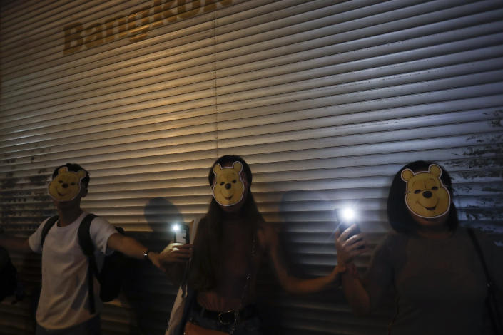 Protesters wear Winnie the Pooh masks during a protest in Hong Kong, Friday, Oct. 18, 2019. Hong Kong pro-democracy protesters are donning cartoon/superhero masks as they formed a human chain across the semiautonomous Chinese city, in defiance of a government ban on face coverings. (AP Photo/Mark Schiefelbein)