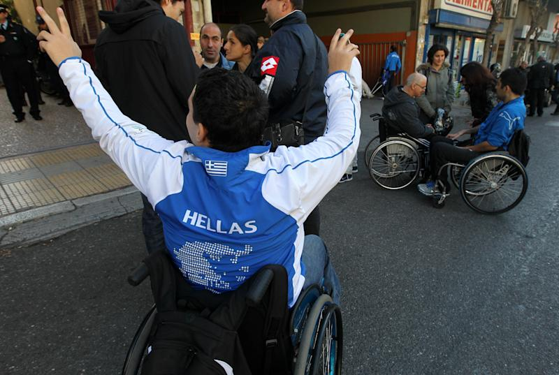 Greek athletes with special needs, including former Paralympic medalists, protest outside the Culture Ministry in Athens on Thursday, Nov 25, 2010. Protesters accuse the Socialist government of slashing funding for sports involving people with special needs, and claim former Paralympic athletes are still owed bonuses for past achievements. Greece is mired in a deep financial crisis, after running up a vast public debt and budget deficit. (AP Photo/Petros Giannakouris)