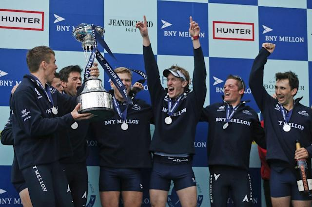 Members of the Oxford University's boat race crew celebrate with the trophy after their win against Cambridge University at the end of their 160th annual Boat Race on the River Thames, London, Sunday, April 6, 2014. The traditional boat race is a hotly contested point of honor between Oxford and Cambridge universities, and Cambridge still leads the series 81-78, with one tie. (AP Photo/Sang Tan)