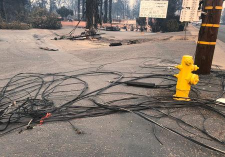 FILE PHOTO: Downed power and utility lines are scattered on pavement following the deadly Camp Fire in Paradise, California, U.S., November 12, 2018. REUTERS/Sharon Bernstein