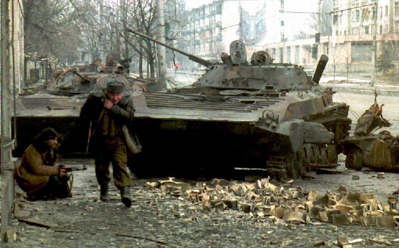A Chechen fighter runs for cover as another hides behind a destroyed Russian tank during fighting in Grozny, Russia, January 8, 1994