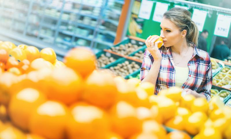 Closeup of late 20's attractive blond woman choosing some fruit in a supermarket. She's next to arranged stack of oranges and lemons, holding an orange and smelling it. Carrying red shopping basket.