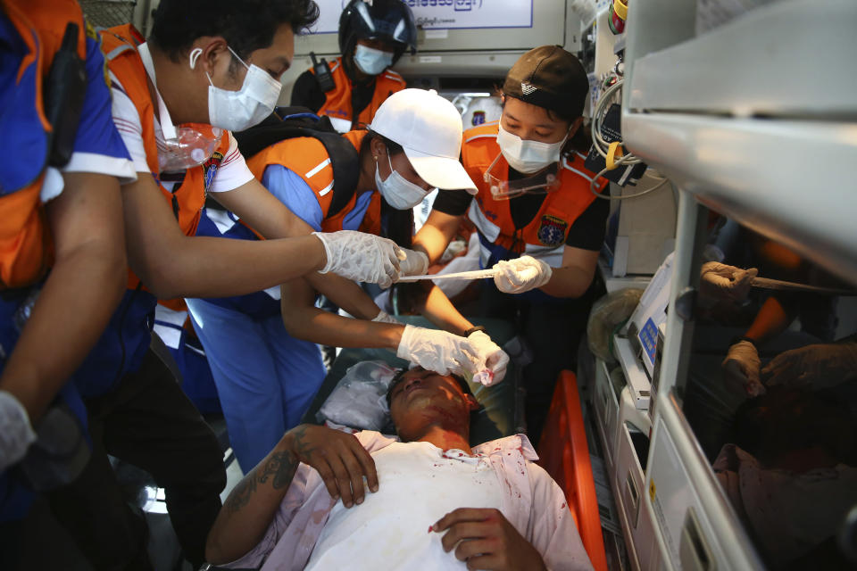 Paramedics tend to an injured protester during a demonstration against the military coup in Mandalay, Myanmar, Friday, Feb. 26, 2021. (AP Photo)