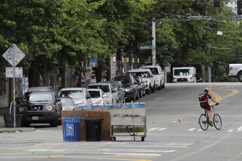 A cyclist rides past what remains of makeshift barricades that were put in place by protesters at the intersection of 10th Ave. and Pine St., Tuesday, June 30, 2020 after Seattle Department of Transportation workers removed concrete barricades from the intersection at the CHOP (Capitol Hill Occupied Protest) zone in Seattle. The area has been occupied by protesters since Seattle Police pulled back from their East Precinct building following violent clashes with demonstrators earlier in the month. (AP Photo/Ted S. Warren)