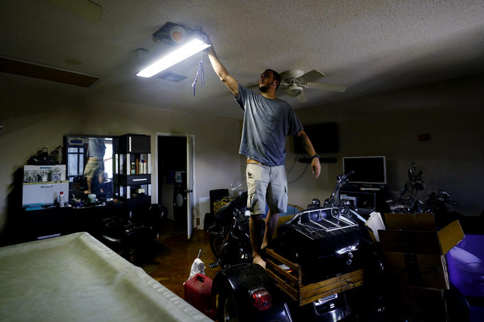 In the wake of Hurricane Ida, Donnie Pearson adjust a light at his home after power was restored to his neighborhood, Wednesday, Sept. 1, 2021, in New Orleans, La. Most of New Orleans remains with power. (AP Photo/Eric Gay)