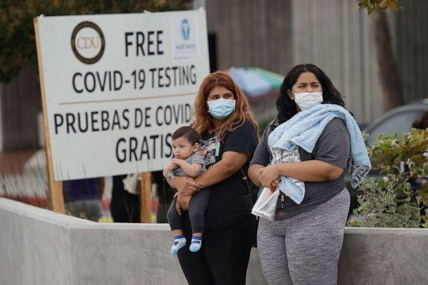 PHOTO: Two women and a child wait to take a coronavirus test at a mobile testing site at the Charles Drew University of Medicine and Science Wednesday, July 22, 2020, in Los Angeles. (Marcio Jose Sanchez/AP)