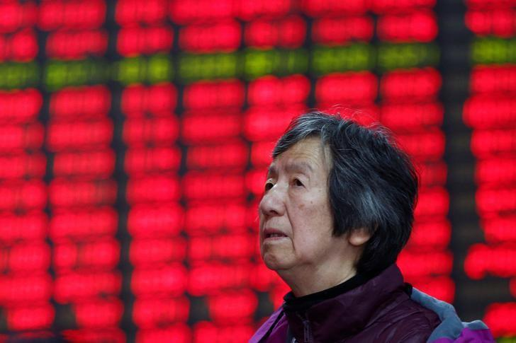 An investor looks at an electronic board showing stock information on the first trading day after the New Year holiday at a brokerage house in Shanghai