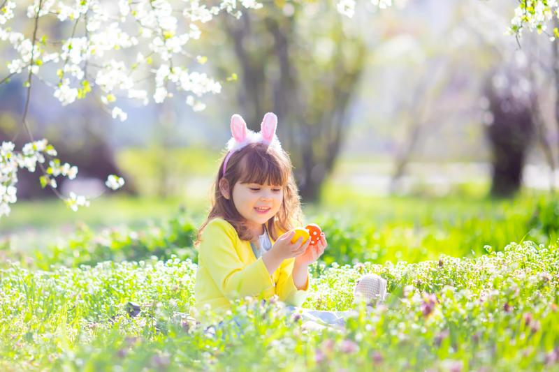 Cute little girl with curly hair wearing bunny ears and summer dress having fun during Easter egg hunt relaxing sitting at the grass and playing with colorful easter eggs in the blooming garden on a sunny spring day