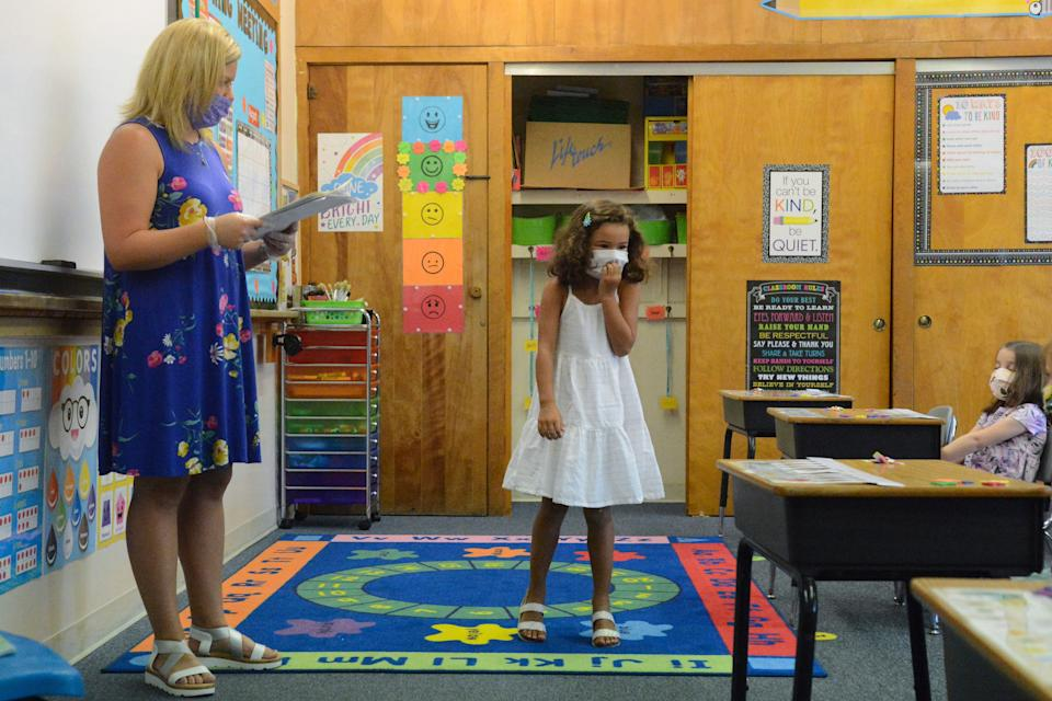 Adyson Snowell walks to the front of the class Aug. 27 as teacher Ashley Thompson looks over what Adyson wrote about herself during kindergarten orientation at St. Nicholas Ukrainian Catholic School in Minersville, Pennsylvania.