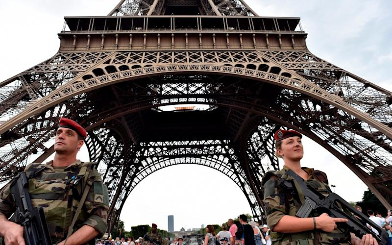 Armed French soldiers of the 35th RAP (35e regiment d'artillerie parachutiste), part of Operation Sentinelle, patrol under at the Eiffel tower in Paris - AFP