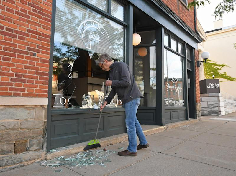 Jeff Kidder, 55, cleans up broken glass and debris in front of a building he owns in downtown Erie, Pa., on May 31. The damage occurred during social unrest after the death of George Floyd, a black man, at the hands of Minneapolis police on May 25. The building houses two businesses, including the Ember + Forge coffee shop, and 10 apartments.