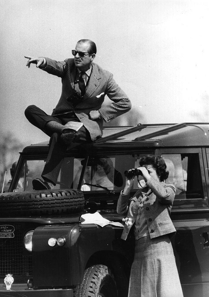 <p>Watching the Badminton Horse Trials, with the Queen using binoculars and the Duke of Edinburgh sat on top of a Land Rover.</p>