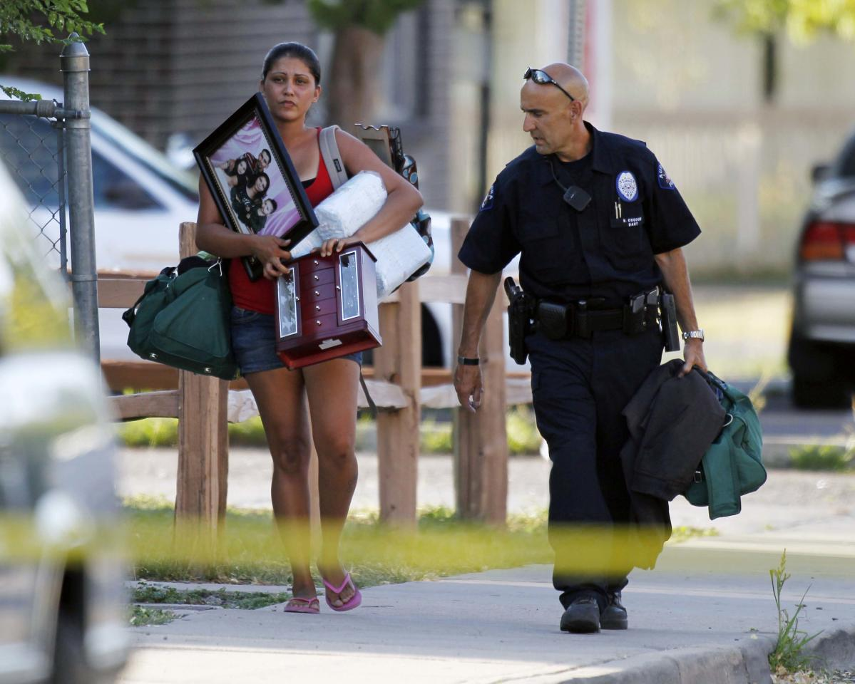 "An Aurora police officer, right, assists a woman carry her belongings from her home near the apartment of alleged gunman James Holmes Friday, July 20, 2012 in Aurora, Colo. Authorities report that 12 died and more than three dozen people were shot during an assault at the theatre during a midnight premiere of ""The Dark Knight."" (AP Photo/Alex Brandon)"