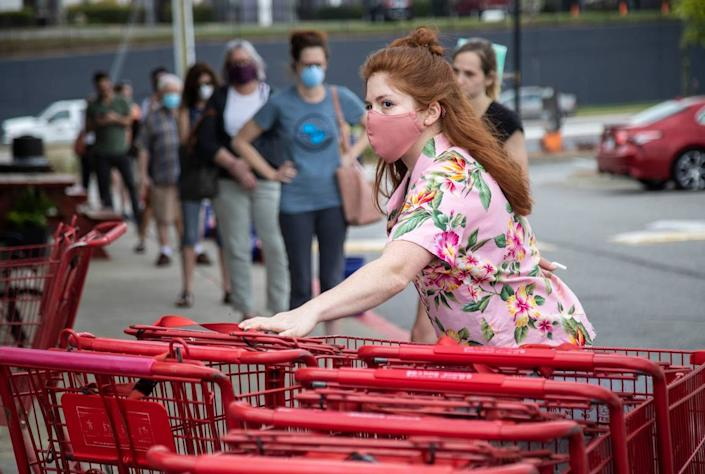 Grocery worker Jody Alexander positions and sanitizes carts at Trader Joe's in Raleigh Tuesday, April 7, 2020. The store is limiting 40 customers in the store at once as customers are asked to adhere to social distancing standards while waiting in lines.