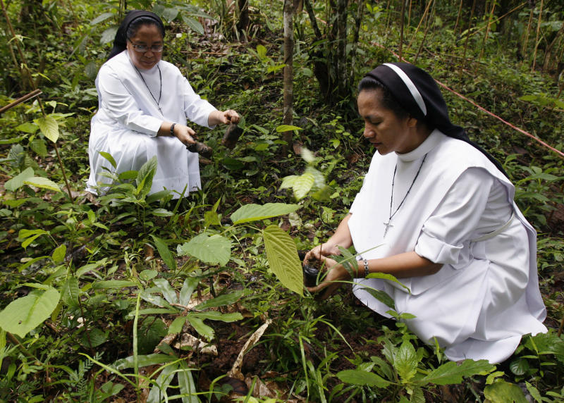 FILE PHOTO: Catholic nuns plant a mahogany tree sapling during the Feast of the Forest event at Cagueban town, Palawan City, Philippines June 30, 2012. The annual event, a massive tree planting exercise, was started in 1991 to raise awareness on environmental issues, in Palawan city. REUTERS/Romeo Ranoco