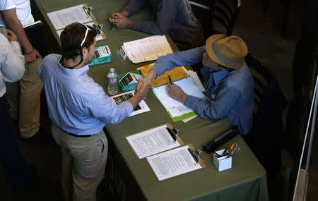 A job applicant (L) shakes hands with a recruiter at the Terrapin Care Station company booth at the CannaSearch cannabis industry job fair in downtown Denver September 16, 2014. REUTERS/Rick Wilking