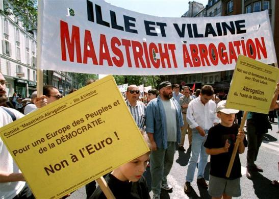 """Demonstrators asking for the annulment of the Maastricht treaty march in the streets of Paris holding banners reading, """"For a democratic Europe for the people, No to the Euro"""" on May 16, 1998."""