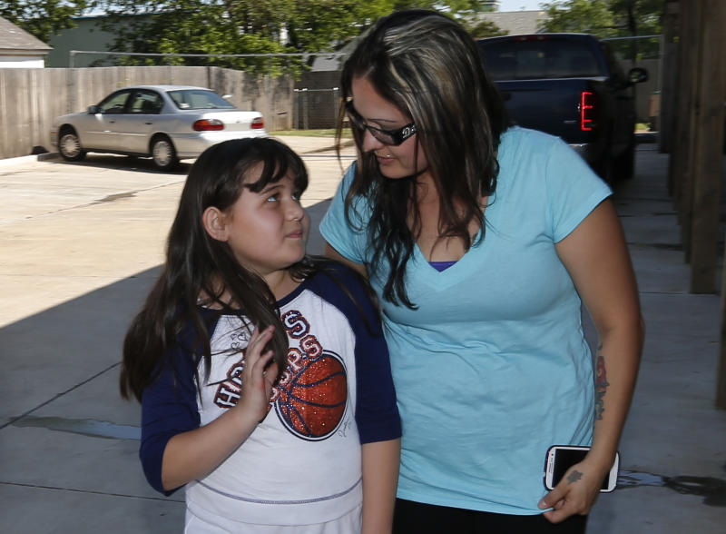 Jazmin Rodriguez, left, looks up at her mother, LaTisha Garcia, right, following an interview in Moore, Okla., Thursday, May 23, 2013. Garcia carried her injured daughter away from a school that was hit by a tornado on Monday. (AP Photo/Sue Ogrocki)
