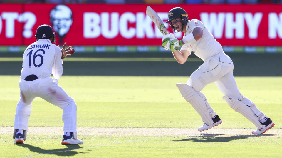Australia's Tim Paine hits at the ball at India's Mayank Agarwal during play on the first day of the fourth cricket test between India and Australia at the Gabba, Brisbane, Australia, Friday, Jan. 15, 2021. (AP Photo/Tertius Pickard)