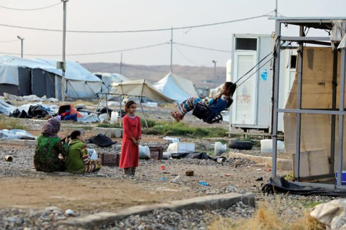 A girl plays on a makeshift swing at Hammam Al-Alil camp where displaced Iraqis prepare to be evacuated, south of Mosul
