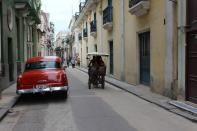 FILE PHOTO: A bicycle taxi passes by a parked vintage American car in Havana