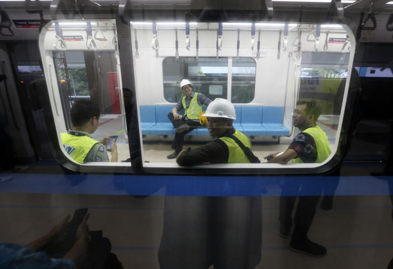 In this Feb. 21, 2019, photo, workers sit inside Mass Rapid Transit (MRT) during a trial run in Jakarta, Indonesia. Commuting in the gridlocked Indonesian capital will for some involve less frustration, sweat and fumes when its first subway line opens later this month. The 10-mile system running south from Jakarta's downtown is the first phase of a development that if fully realized will plant a cross-shaped network of stations in the teeming city of 30 million people. (AP Photo/Achmad Ibrahim)