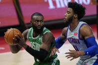 Boston Celtics guard Jaylen Brown looks to pass the ball as Detroit Pistons guard Saddiq Bey (41) defends during the first half of an NBA basketball game Friday, Jan. 1, 2021, in Detroit. (AP Photo/Carlos Osorio)