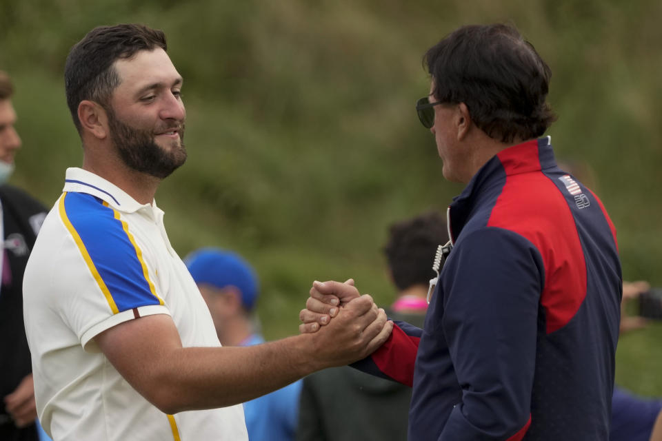 Team Europe's Jon Rahm shakes hands with Team USA assistant captain Phil Mickelson after the Ryder Cup matches at the Whistling Straits Golf Course Sunday, Sept. 26, 2021, in Sheboygan, Wis. (AP Photo/Charlie Neibergall)