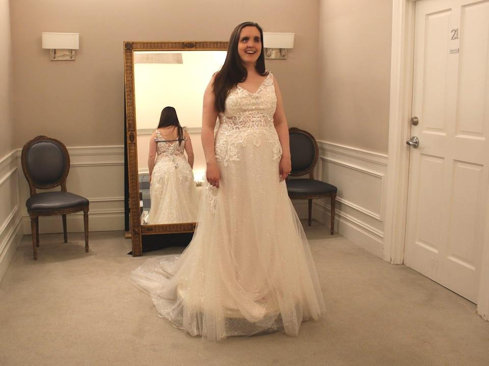 A bride stands on a pedestal in a wedding dress in a bridal store.