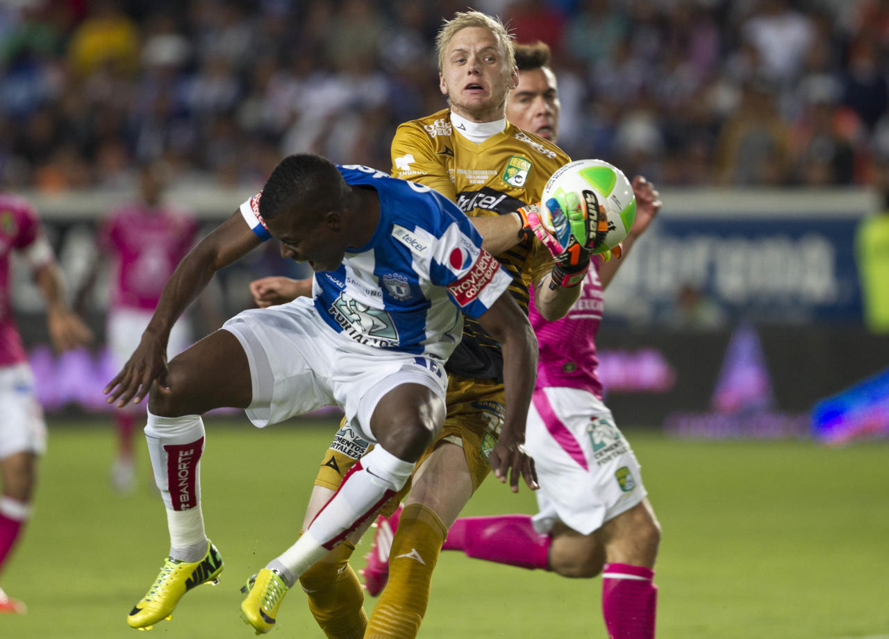 Pchuca's Enner Valencia, left, fights for the ball with Leon's William Yarbrough during the final match of the Mexican soccer league in Pachuca, Sunday, May 18, 2014. (AP Photo/Christian Palma)