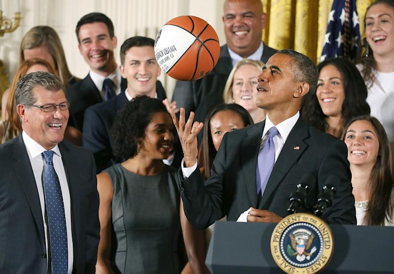 Barack Obama tosses up a basketball given to him by coach Geno Auriemma (L) while honoring the 2015 NCAA Women's Basketball Champion University of Connecticut Huskies during a ceremony in the East Room at White House September 15, 2015 in Washington, DC. Obama honored the Huskies for winning their third consecutive title with 10 overall. (Photo by Mark Wilson/Getty Images)
