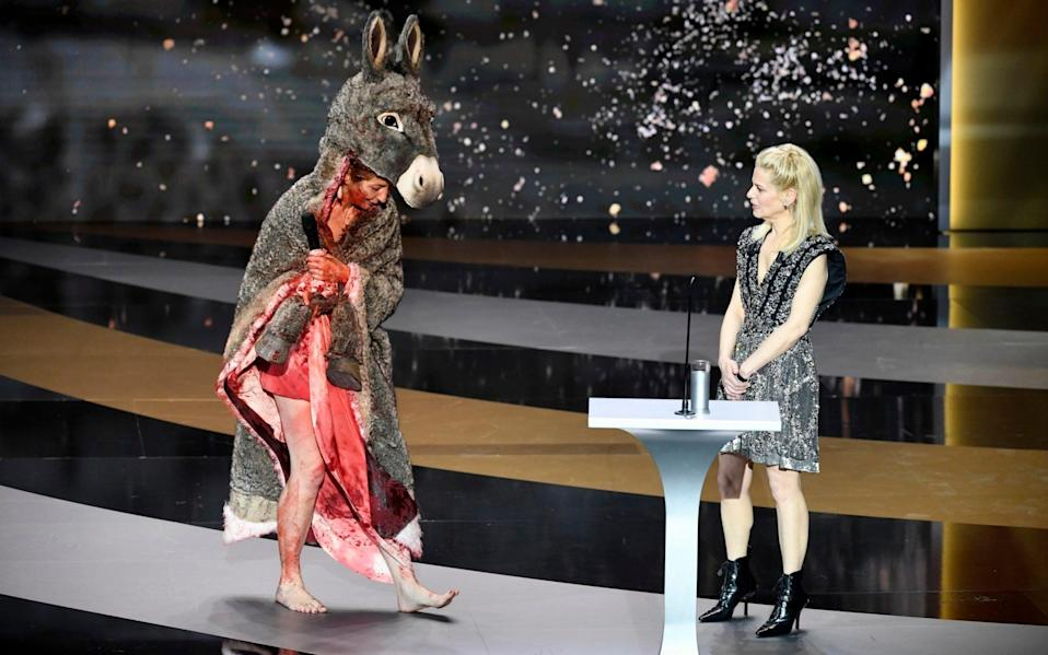"""Corinne Masiero (L) delivers a speech wearing a """"Peau d'Ane"""" costume next to French actress and Master of Ceremony Marina Fois - Bertrand Guay/AFP"""