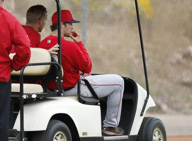 Los Angeles Angels' C.J. Wilson, right, is taken back to the clubhouse by medical personnel after being struck in the head with a line drive while he was pitching during spring training baseball practice on Tuesday, Feb. 25, 2014, in Tempe, Ariz. (AP Photo/Ross D. Franklin)