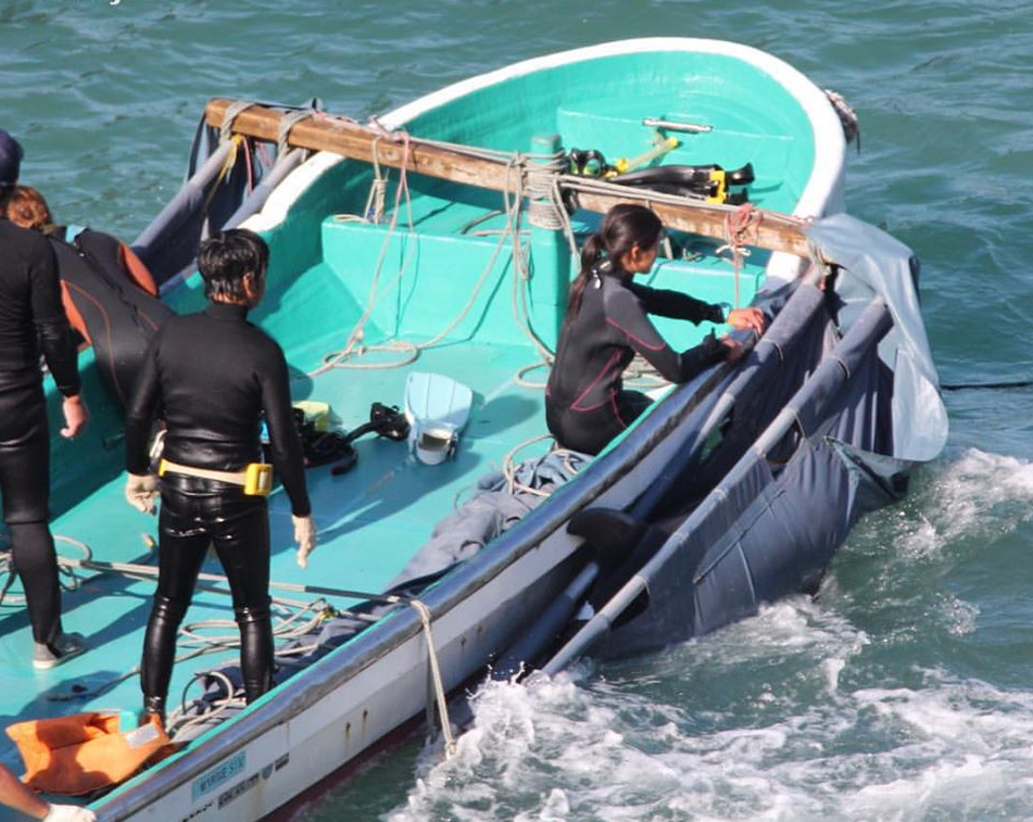 Four Japanese people in wetsuits are in a boat, catching a dolphin.