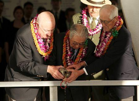 """Dr. Hiroya Sugano(c), former World War Two B25 bomber pilot Jack DeTour(L) and former World War Two Japanese fighter pilot Shiro Wakita pour bourbon whiskey into the """"Remembrance Well"""" aboard the USS Arizona Memorial during the """"Blackened Canteen"""" ceremony honoring the 74th anniversary of the attack on Pearl Harbor at the World War II Valor in the Pacific National Monument in Honolulu, Hawaii December 6, 2015. REUTERS/Hugh Gentry"""