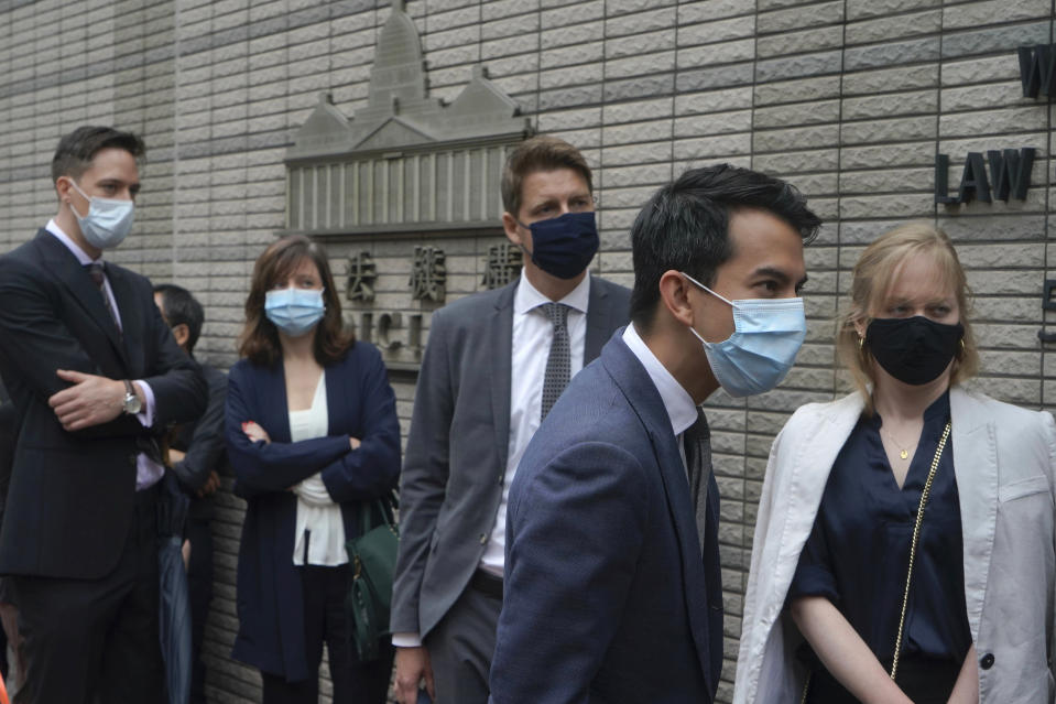 Diplomatic representatives from left, the Netherlands, France, Sweden, Australia and Canada wait to enter a court in Hong Kong Friday, April 16, 2021. Seven of Hong Kong's leading pro-democracy advocates, including 82-year-old veteran activist Martin Lee and pro-democracy media tycoon Jimmy Lai, are expected to be sentenced Friday for organizing a march during the 2019 anti-government protests that triggered an overwhelming crackdown from Beijing.(AP Photo/Kin Cheung)