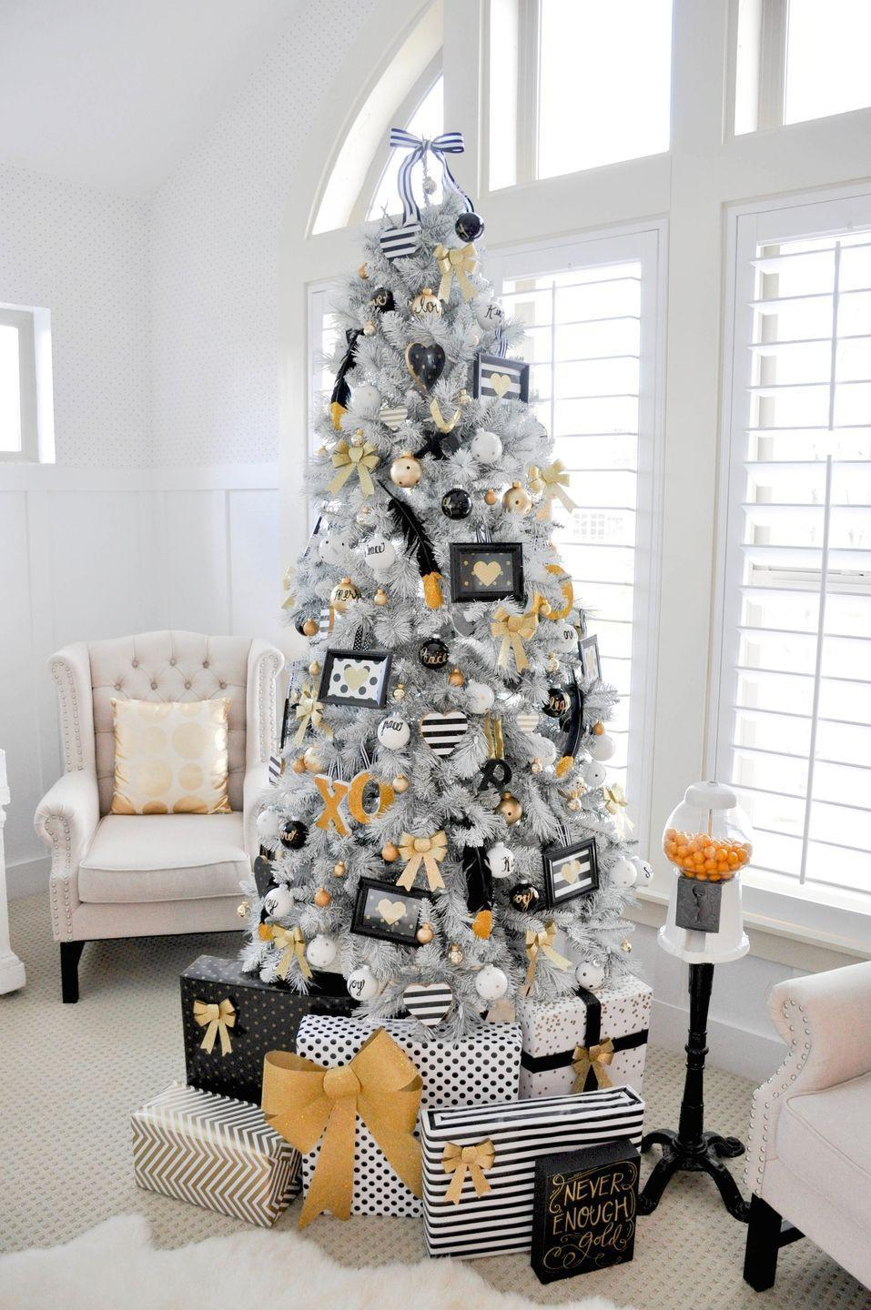 "<p>Black, white, and gold is a timeless color scheme. This tree from <a href=""http://karaspartyideas.com/2014/11/black_white_gold_christmas_tree.html"" rel=""nofollow noopener"" target=""_blank"" data-ylk=""slk:Kara's Party Ideas"" class=""link rapid-noclick-resp"">Kara's Party Ideas</a> is covered with gold-dipped feathers, photo frames, bows, and even presents wrapped to match. </p>"
