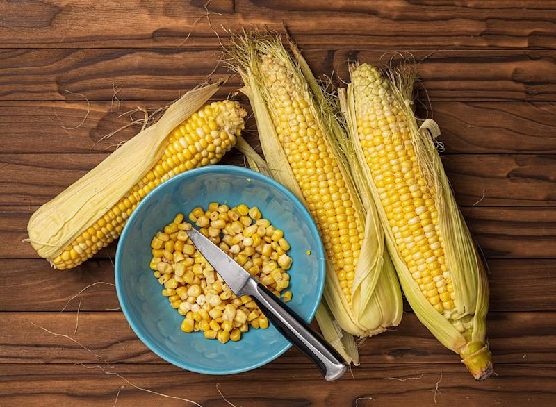 Shucking corn with a knife in a bowl
