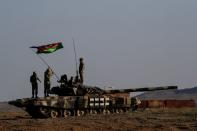 Azerbaijani soldiers who are civilians recalled for duty hang a national flag to a tank during a training at a military training and deployment center near the city of Ganja