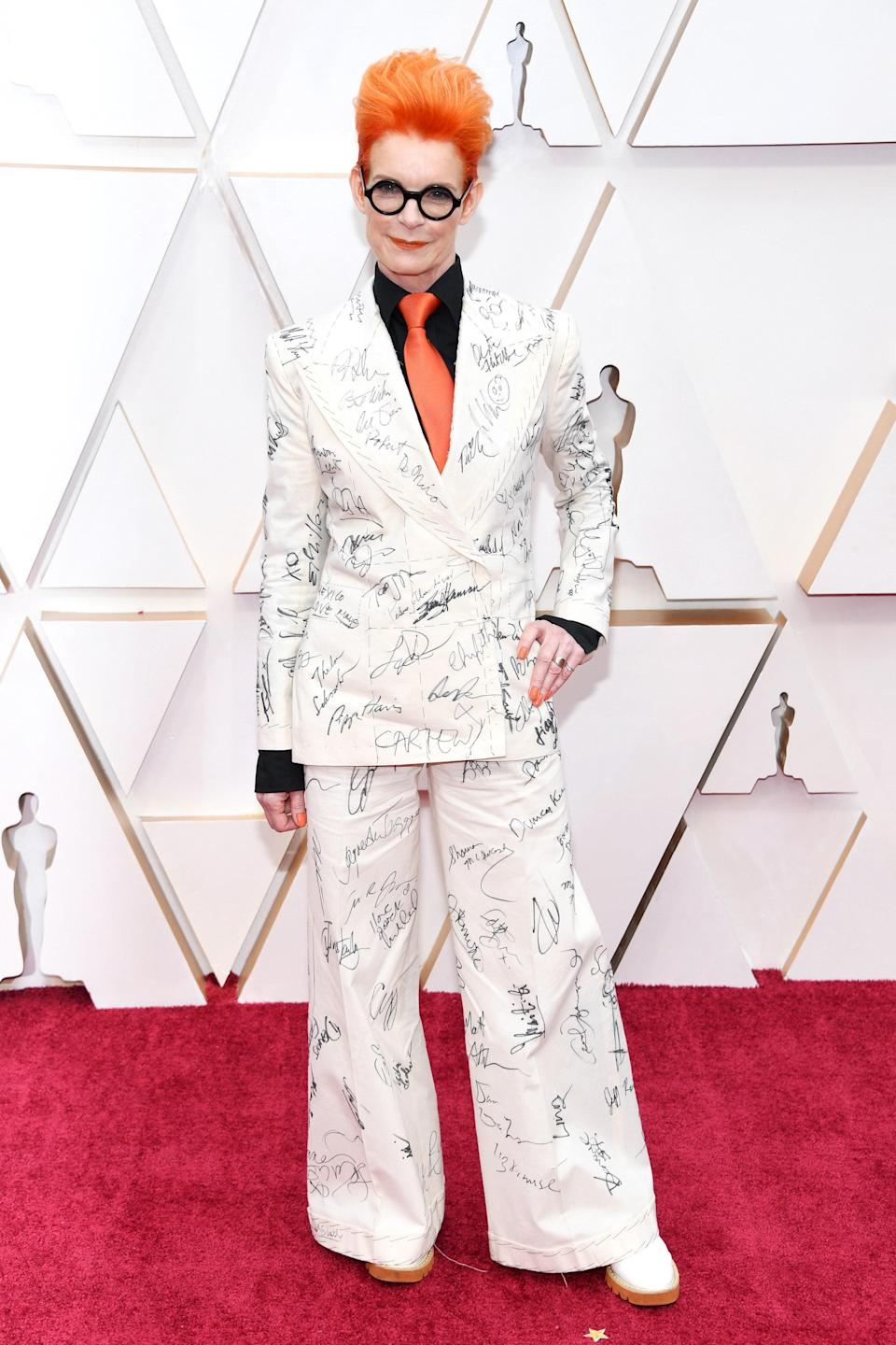 """Veteran British costume designer Sandy Powell developed her Oscars look throughout awards season in 2020, but not by working closely with a label. Instead, Powell hit up the various ceremonies in the <a href=""""https://www.vogue.com/vogueworld/article/sandy-powell-baftas-oscars-suit-derek-jerman?mbid=synd_yahoo_rss"""" rel=""""nofollow noopener"""" target=""""_blank"""" data-ylk=""""slk:same cream suit"""" class=""""link rapid-noclick-resp"""">same cream suit</a>, having different A-list stars sign the suit along the way. After the Oscars, she auctioned off the signed suit for an Art Fund charity, which hoped to help preserve and maintain the home of late friend and mentor Derek Jarman, an English filmmaker and artist. It ended up <a href=""""https://www.irishnews.com/magazine/entertainment/2020/03/11/news/suit-signed-by-a-listers-makes-16-000-to-help-jarman-cottage-bid-1865529/"""" rel=""""nofollow noopener"""" target=""""_blank"""" data-ylk=""""slk:fetching"""" class=""""link rapid-noclick-resp"""">fetching</a> roughly $22,230 USD at auction, and featured signatures from Robert De Niro, Renée Zellweger, and more."""