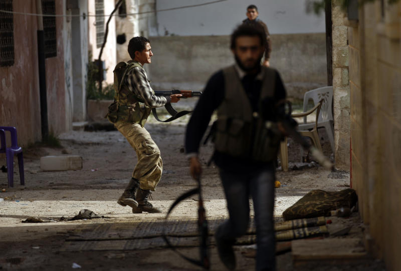 In this Saturday, Nov. 17, 2012 file photo, a Syrian fighter fires his weapon during clashes with army forces on the outskirts of Idlib, Syria. Through mid-2012, rebel power grew and Assad's army ramped up its response. Relentless government shelling leveled neighborhoods and killed hundreds. Regular reports emerged of mass killings by the regime or thugs loyal to it, pushing more Syrians toward armed struggle. The government, which considers the opposition terrorist gangs backed by foreign powers, denied any role, and does not respond to requests for comment on its military. The rebels, too, were accused of atrocities. (AP Photo/ Khalil Hamra, File)