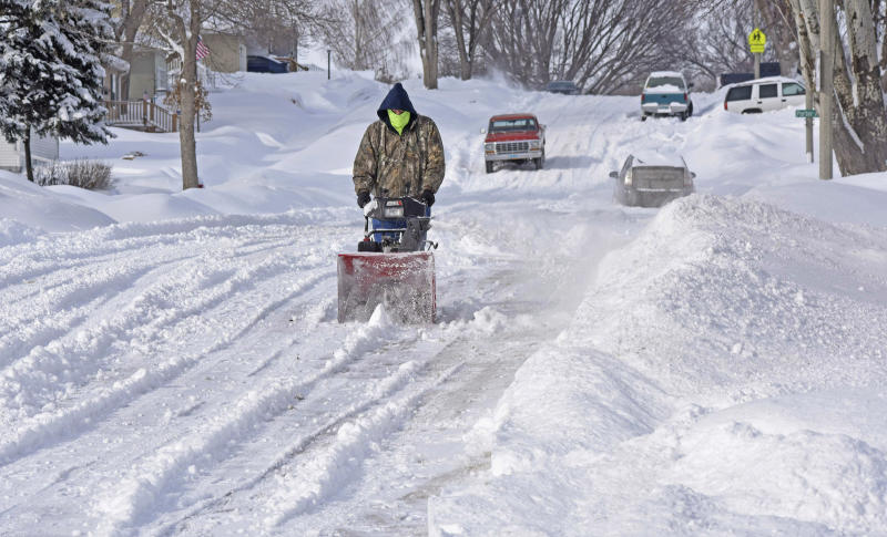 "Randy Ohlhauser clears snow from the street next to his home on Saturday, March 9, 2019, in Bismarck, N.D., to make room for evening guests to park their vehicles. ""We're having a pinochle card party,"" said Ohlhauser ""and there's no place to put this snow."" (Tom Stromme/The Bismarck Tribune via AP)"