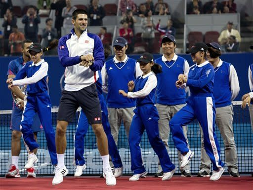 """Serbia's Novak Djokovic, center, performs South Korean rapper PSY's """" Gangnam Style"""" dance with volunteers on a court after a prize presentation for the men's singles final match of the China Open tennis tournament in Beijing Sunday, Oct. 7, 2012. Djokovic won the China Open tennis tournament, defeated Jo-Wilfried Tsonga 7-6, 6-2. (AP Photo/Andy Wong)"""