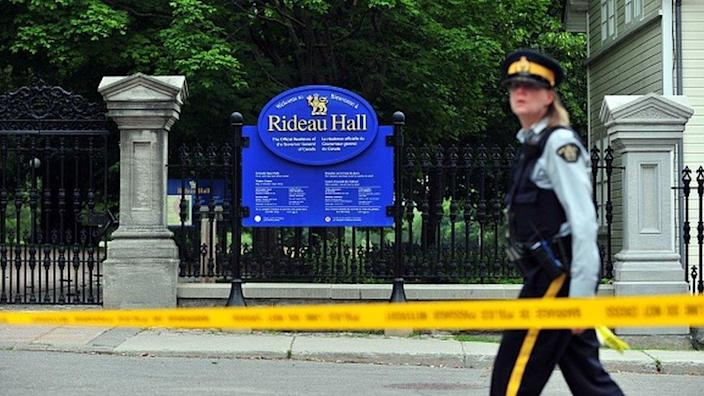 A Canadian police officer walks by Rideau Hall near the grounds of the Ottawa estate