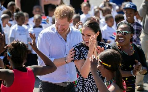 The Duke and Duchess of Sussex dance during a visit to Nyanga township in Cape Town in September - Credit: REX