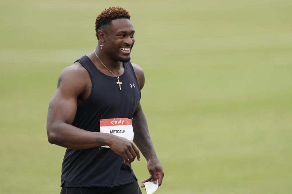 Seattle Seahawks wide receiver DK Metcalf smiles after competing in the second heat of the men's 100-meter dash prelim during the USATF Golden Games at Mt. San Antonio College Sunday, May 9, 2021, in Walnut, Calif. (AP Photo/Ashley Landis)