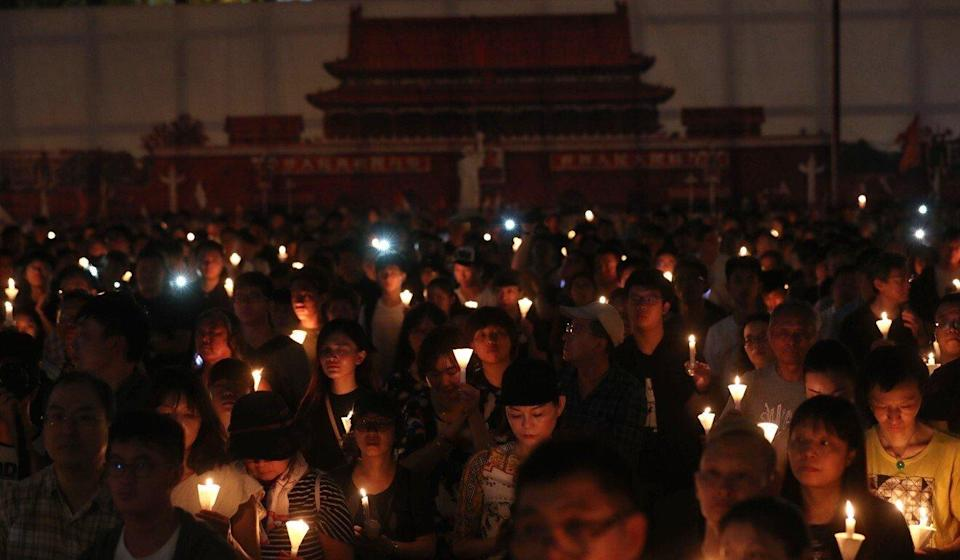 People raise their candles during the June 4 vigil at Victoria Park in 2019. Photo: Sam Tsang